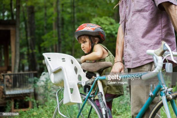 midsection of man with daughter on bicycle in backyard - man tied to chair stock photos and pictures