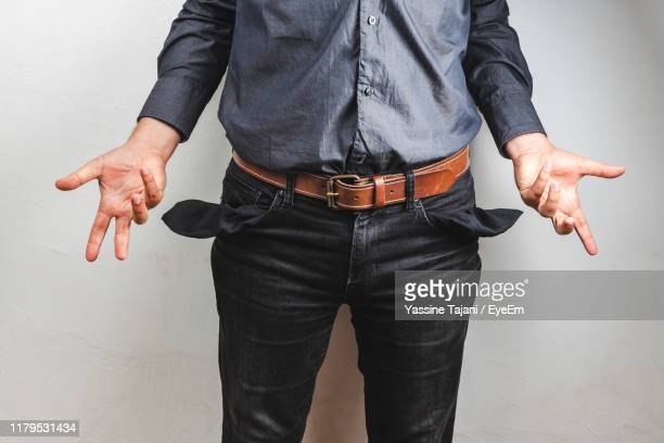 midsection of man with empty pockets standing against wall - pocket stock pictures, royalty-free photos & images