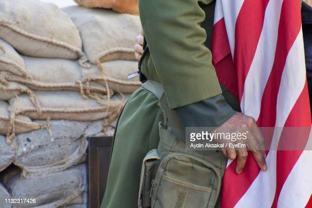 Midsection Of Man With Flag Against Sack Heap
