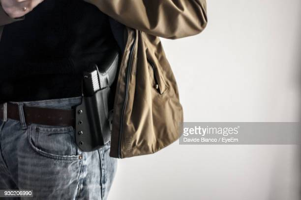 midsection of man with gun holster against white background - handgun stock pictures, royalty-free photos & images