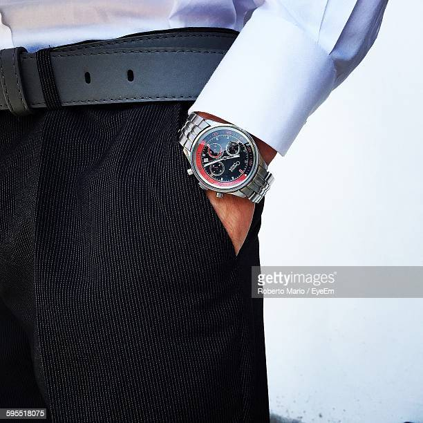 midsection of man with hand in pocket against wall - hands in pockets stock photos and pictures