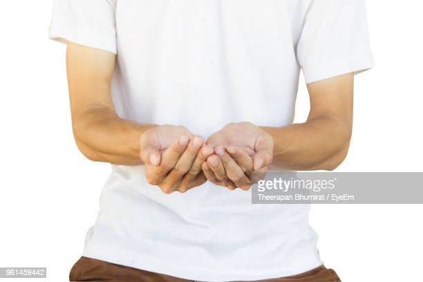 Midsection Of Man With Hands Cupped Standing Against White Background