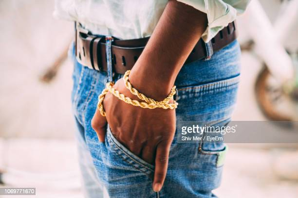 midsection of man with hands in pocket wearing gold bracelet - riem persoonlijk accessoire stockfoto's en -beelden