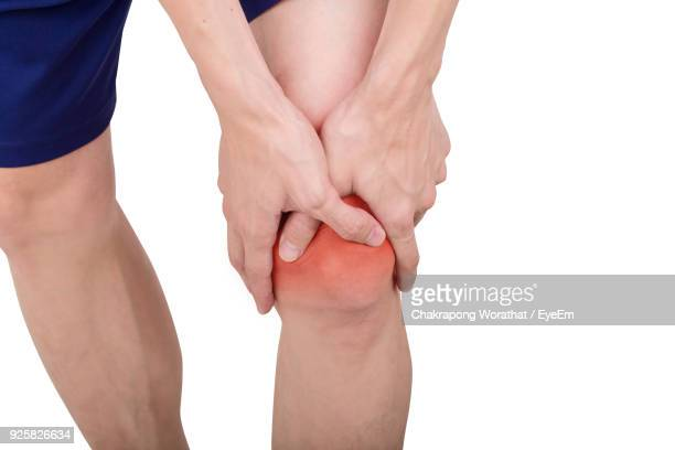 Midsection Of Man With Knee Pain Against White Background