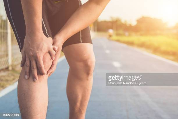 midsection of man with knee pain standing on road - pain foto e immagini stock
