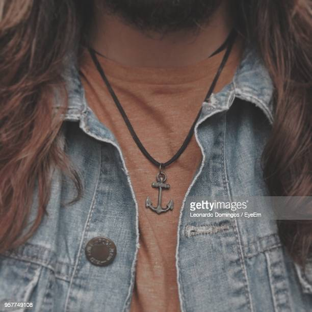 midsection of man with long hair wearing denim jacket and anchor pendant - ペンダント ストックフォトと画像