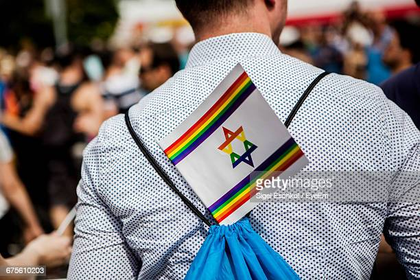 Midsection Of Man With Multi Colored Israeli Flag On Back During Gay Pride Parade