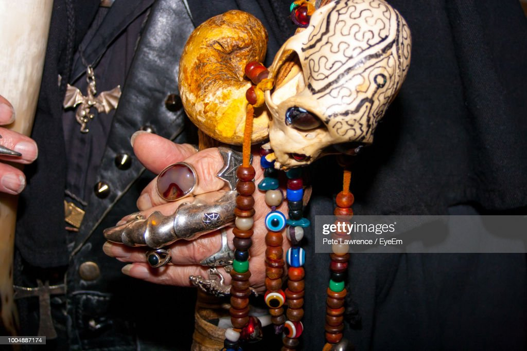 Midsection Of Man With Multi Colored Jewelry And Human Skull : Stock Photo