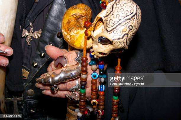 midsection of man with multi colored jewelry and human skull - bones stock photos and pictures