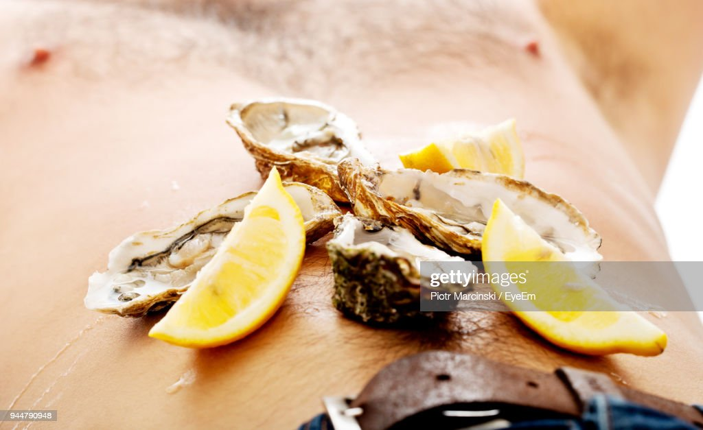 Midsection Of Man With Oysters And Lemon Slices On Belly : Stock Photo