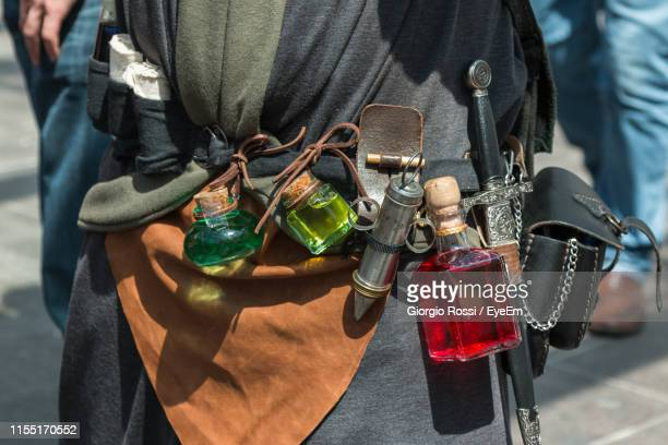 midsection of man with perfume bottles and dagger standing outdoors - dagger stock pictures, royalty-free photos & images