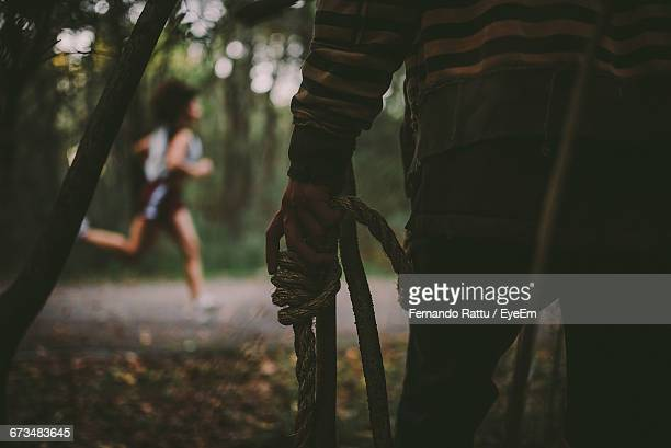 Midsection Of Man With Rope Standing Against Running Woman In Forest