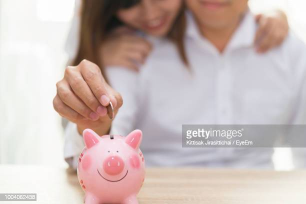 Midsection Of Man With Woman Putting Coin In Piggy Bank