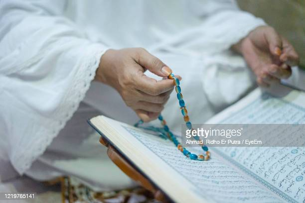 midsection of man working on book - koran stock pictures, royalty-free photos & images