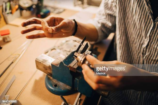 midsection of man working on equipment at desk in workshop - inventor stock pictures, royalty-free photos & images