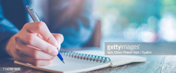 midsection of man writing in book - writing stock pictures, royalty-free photos & images