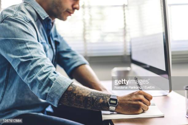 midsection of man writing in book while using computer on table in office - solo un uomo giovane foto e immagini stock