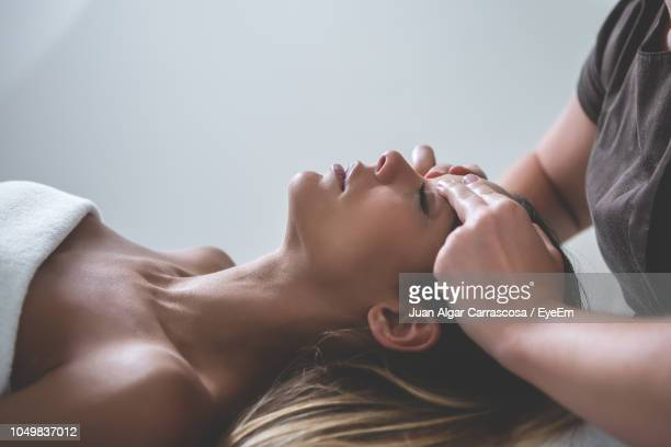midsection of masseur massaging woman lying on bed at spa - health farm stock pictures, royalty-free photos & images