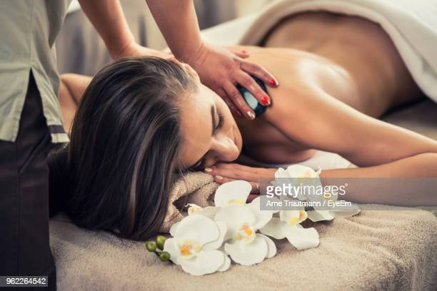 Midsection Of Masseuse Giving Massage To Woman At Spa