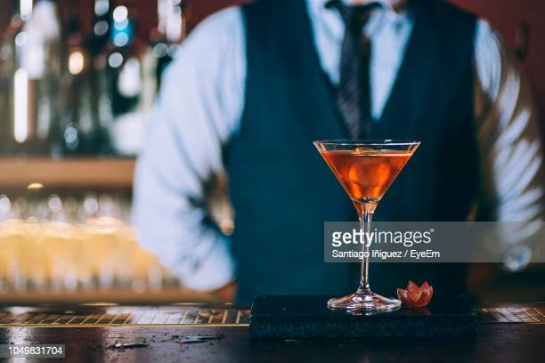 midsection of mature bartender standing by cocktail on bar counter - cocktail stock pictures, royalty-free photos & images