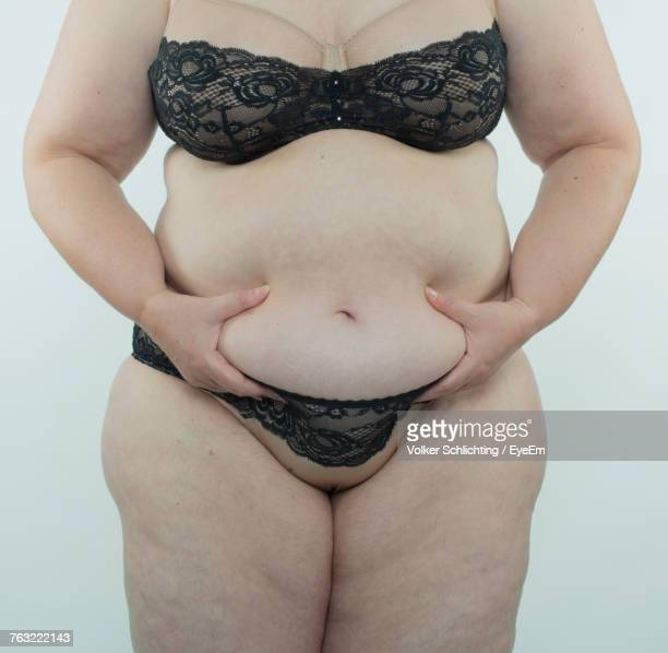 midsection of mature woman holding abdomen against white background - human body part photos et images de collection