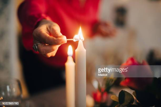 midsection of mature woman igniting candle on dining table in party at home - candle stock pictures, royalty-free photos & images