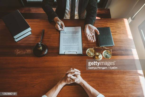 midsection of men discussing on table - law stock pictures, royalty-free photos & images
