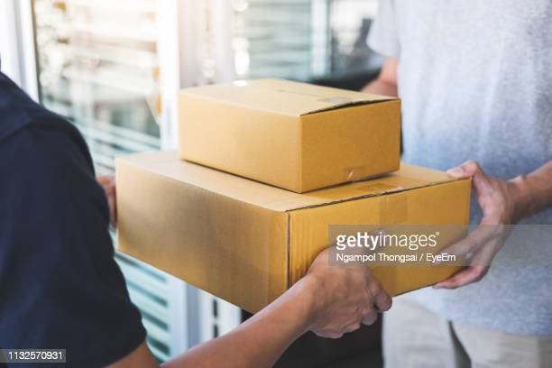 midsection of men holding cardboard boxes outdoors - recevoir photos et images de collection