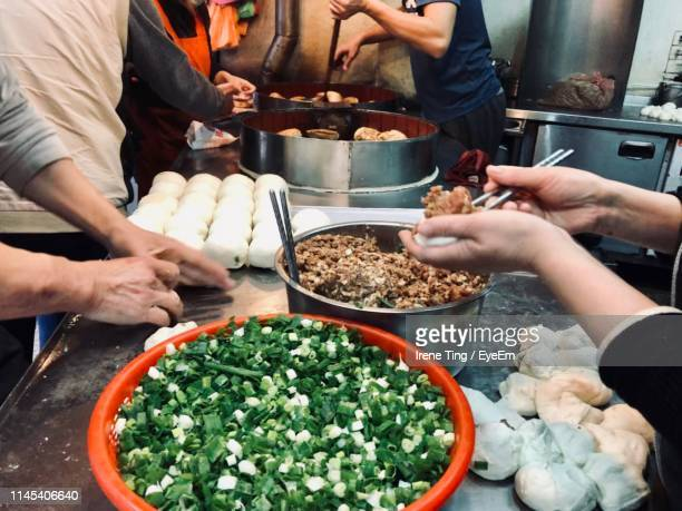 Midsection Of Men Preparing Food In Commercial Kitchen