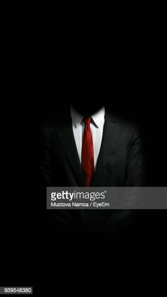 Midsection Of Men Wearing Suit Against Black Background