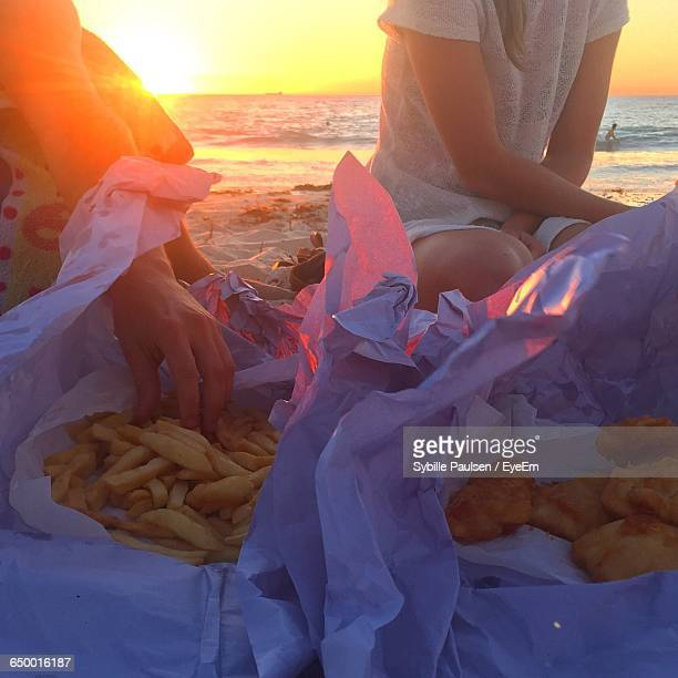 Midsection Of Men With French Fries And Fried Fish At Beach During Sunset