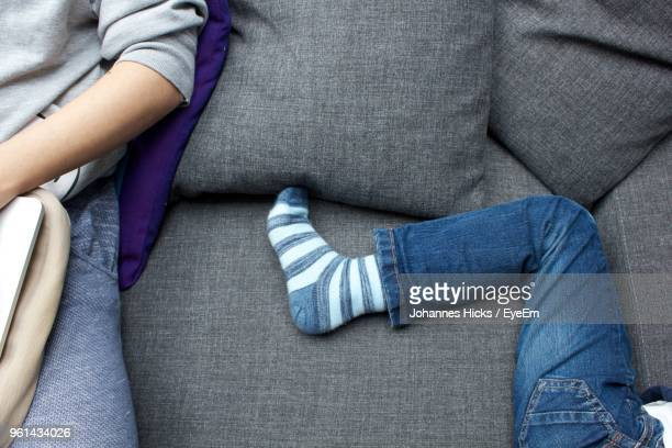 Midsection Of Men With Friend Resting On Sofa At Home