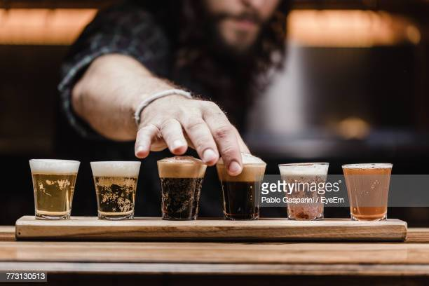 Midsection Of Mid Adult Man Arranging Beer Glass On Table