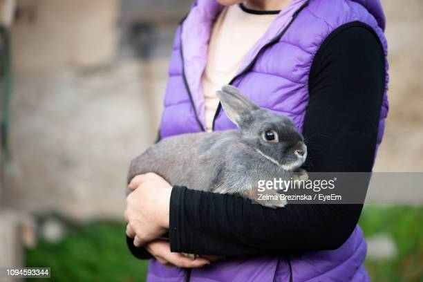 Midsection Of Mid Adult Woman Carrying Cute Rabbit While Standing Outdoors