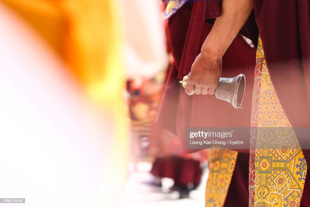 Midsection Of Monk Holding Bell At Temple : Stock Photo