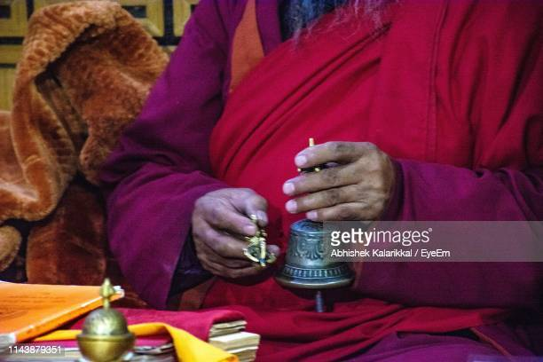 Midsection Of Monk Holding Traditional Bell