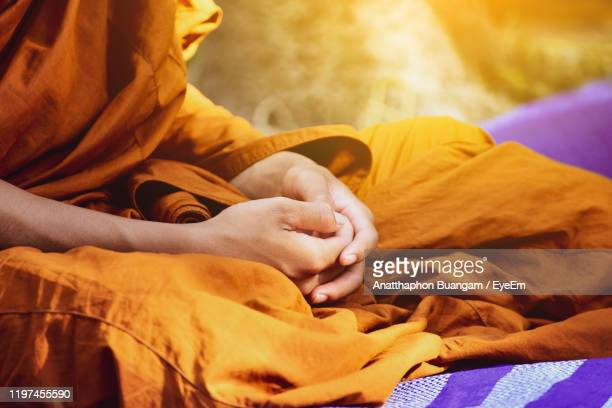 midsection of monk sitting at temple - monk stock pictures, royalty-free photos & images