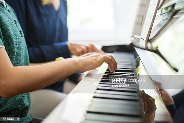 Midsection of mother and son playing piano