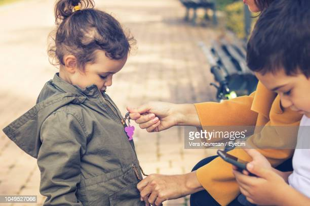 midsection of mother closing zip of daughter jacket with son at park - jacke stock-fotos und bilder