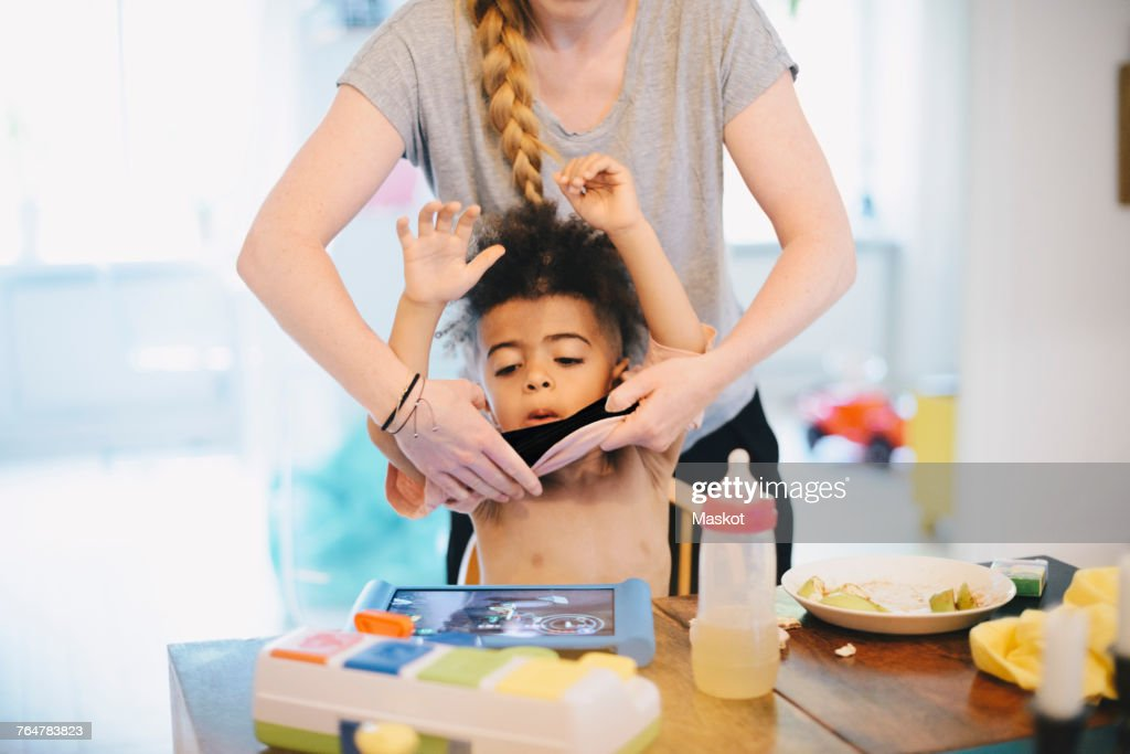 Midsection of mother dressing son at table : Stock Photo