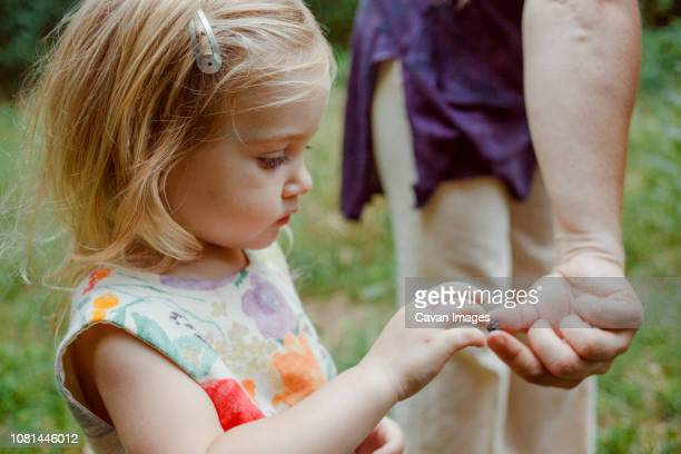 Midsection of mother giving berry to daughter standing in forest