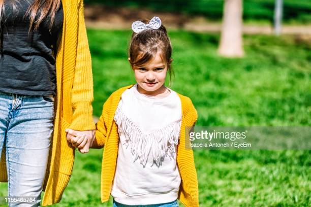 midsection of mother holding cute daughter while standing on grassy field in park - sezione centrale foto e immagini stock