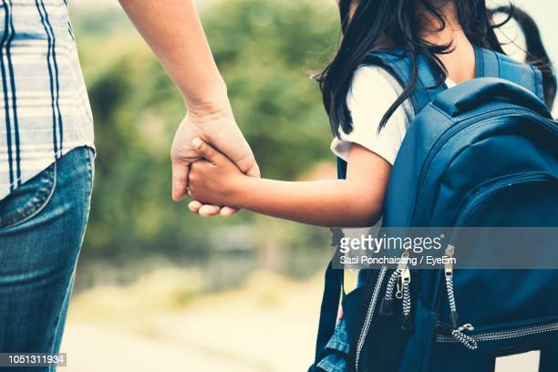 midsection of mother holding daughter hand while taking her to school - riapertura delle scuole foto e immagini stock