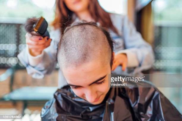 midsection of mother shaving teenage son's head with electric razor at home - shaved stock pictures, royalty-free photos & images