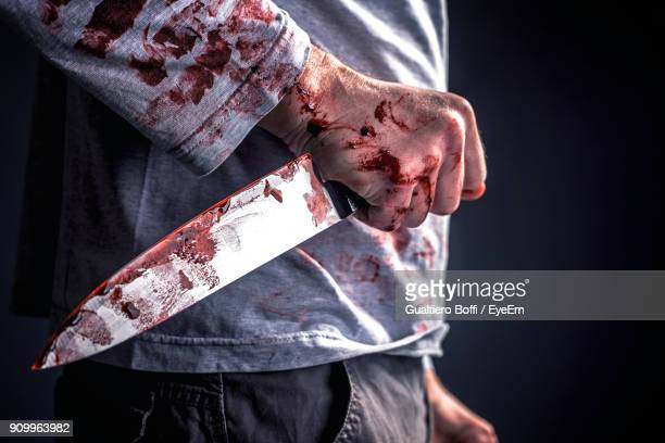 midsection of murderer holding blooded knife against black background - mord stock-fotos und bilder