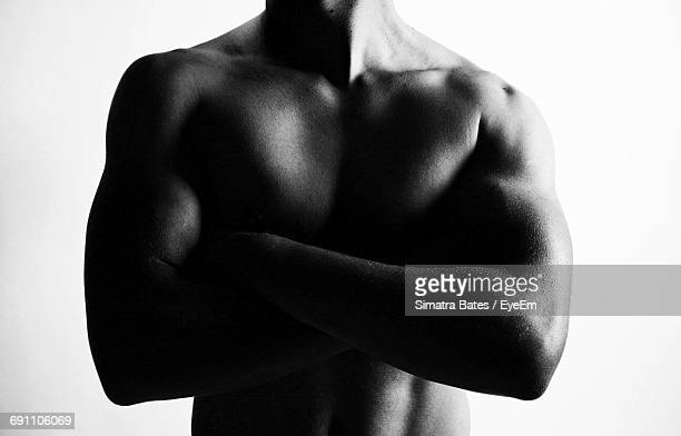 Midsection Of Muscular Build Man Standing Arms Crossed Against White Background