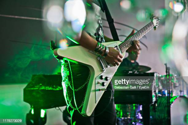 midsection of musician playing guitar at concert - chitarrista foto e immagini stock