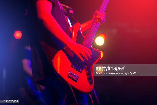 midsection of musician playing guitar in concert - ポップコンサート ストックフォトと画像