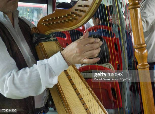 Midsection Of Musician Playing Harp In Bus