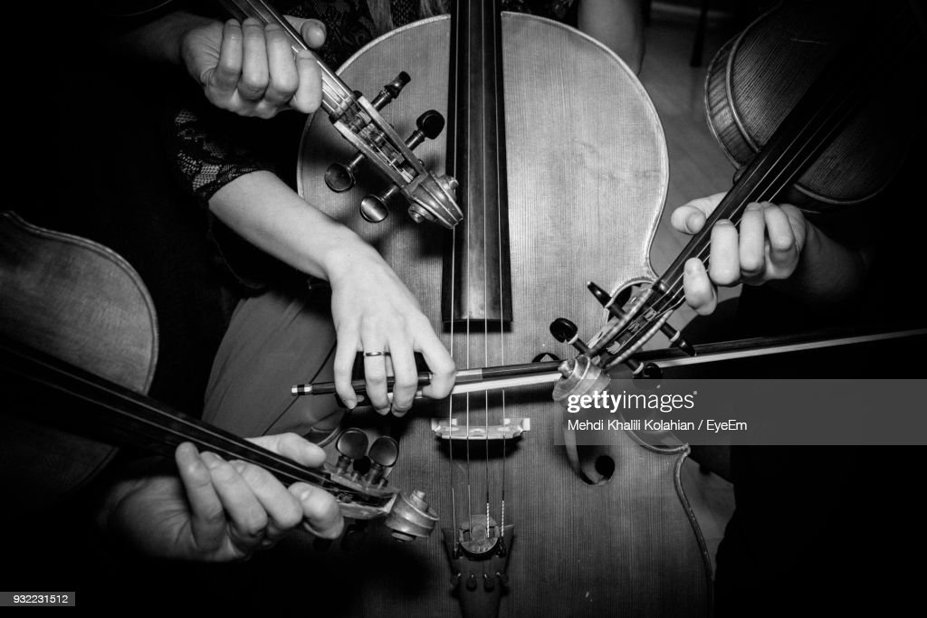 Midsection Of Musicians Playing Cello And Violins : Stock Photo
